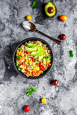 Bowl of bulgur salad with bell pepper, tomatoes, avocado, spring onion and parsley - p300m2023466 by Sandra Roesch