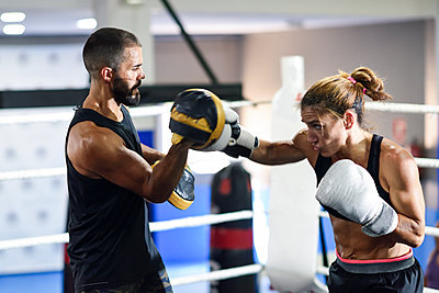 Female boxer sparring with her coach in gym - p300m2180875 by Javier Sánchez Mingorance