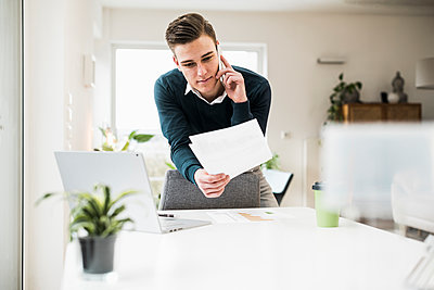 Young businessman holding document talking on smart while leaning on chair in home office - p300m2267477 by Uwe Umstätter
