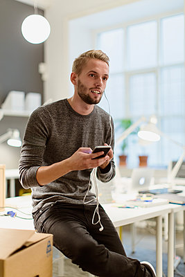 Young businessman looking away while talking on smart phone through in-ear headphones at creative office - p426m1588292 by Kentaroo Tryman