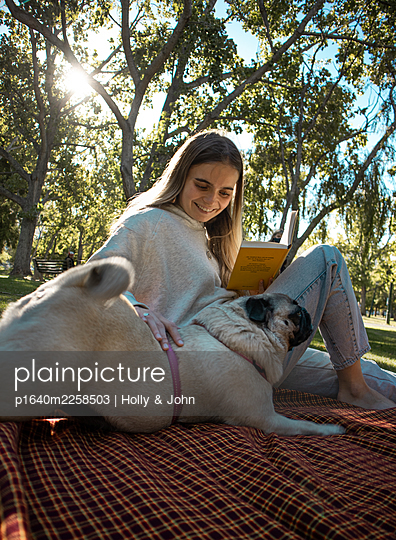Teenage girl and pug in the park - p1640m2258503 by Holly & John