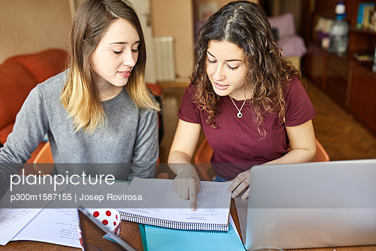 Two female students at desk working and learning together - p300m1587155 von Josep Rovirosa