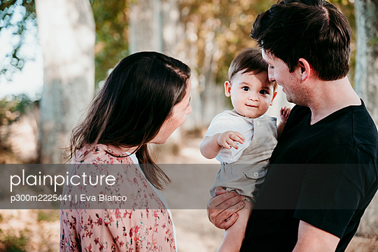 Smiling parents looking at baby while standing outdoors - p300m2225441 by Eva Blanco