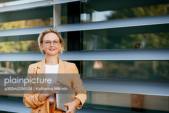 Confident mature businesswoman with laptop against office building - p300m2256124 by Katharina Mikhrin