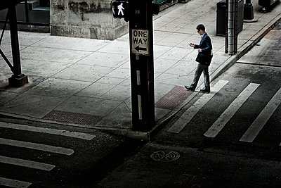 A man walking across a street crossing, looking at a phone in his hand.  - p1100m1095643 by Mint Images