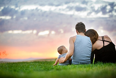 Rear view of family sitting on field during sunset - p1166m1174170 by Cavan Images