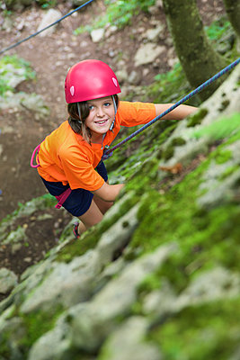 Little girl climbing stone wall in a forest, Pyrenees. - p1166m2136565 by Cavan Images