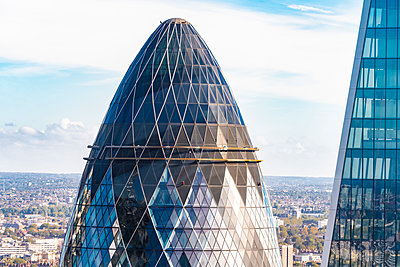 Detail of the Gherkin tower exterior with blue sky - p1166m2136995 by Cavan Images
