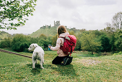 girl sat with her dog looking at a castle in the english countryside - p1166m2279271 by Cavan Images
