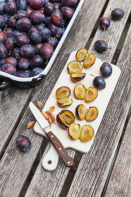 Fresh plums in casserole and chopped plums on chopping board - p300m1568059 by Gaby Wojciech