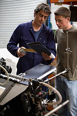 A man training a young man in a printing factory - p30118326f by Ableimages