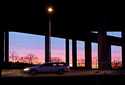 Car under overpass at sunset - p312m672809 by Susanne Walström