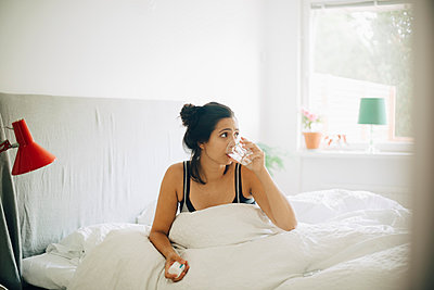 Woman drinking water while holding pills on bed at home - p426m1537136 by Maskot
