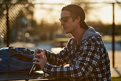Youthful male millenial outside on park bench using tablet - p1362m1553699 by Charles Knox