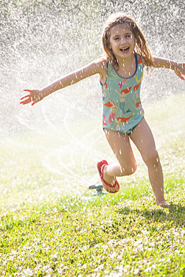 Girl splashing in sprinkler water on lawn - p1427m1553591 by Tetra Images