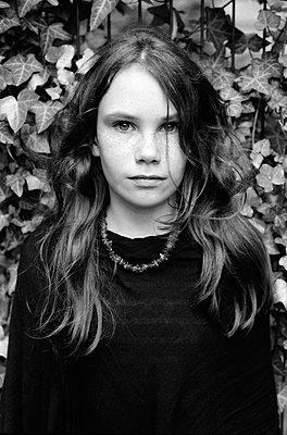 Teenager girl with long hair against ivy - p1648m2245004 by KOLETZKI