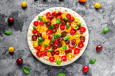 Unbaked pizza with tomatoes and basil leaves - p300m2023986 von Sandra Roesch