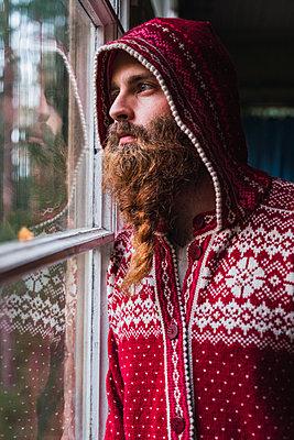 Portrait of pensive man with beard wearing hooded jacket looking out of window - p300m2060879 von Kike Arnaiz