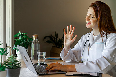 Young female doctor waving hand at patient while providing online consultation from home office - p300m2224892 by VITTA GALLERY