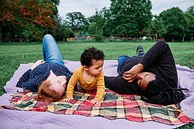 Multi-ethnic family relaxing on picnic blanket at park - p300m2287213 by Angel Santana Garcia