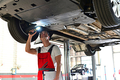 Car mechanic in a workshop checking underbody of a car - p300m950420f by lyzs