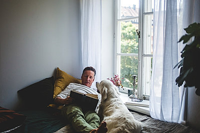 Senior man lying with dog while reading book on bed by window at home - p426m2046388 by Maskot