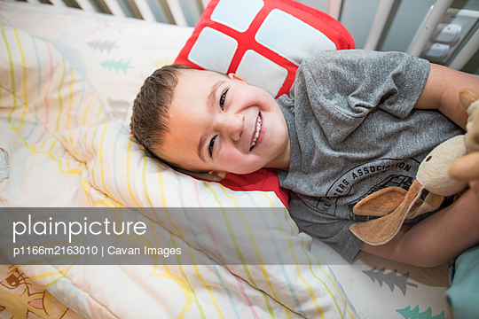 Happy toddler boy resting  head on pillow in bed. - p1166m2163010 by Cavan Images