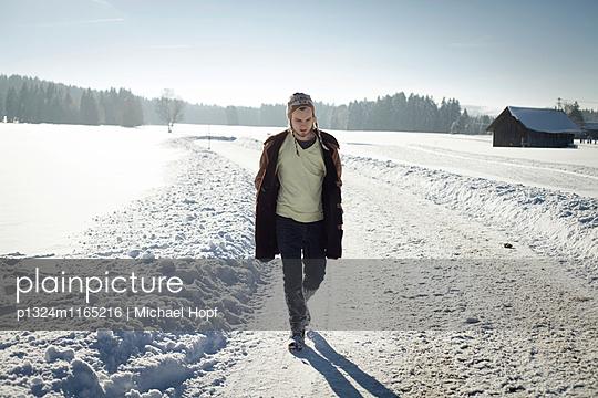 Junger Mann macht einen Spaziergang in Schneelandschaft - p1324m1165216 von michaelhopf
