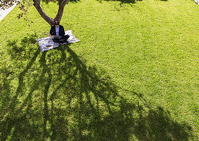 Businessman working, using laptop on blanket below tree in sunny yard - p1023m1406889 by Martin Barraud
