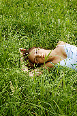 Young woman lying in grass - p1050134 by André Schuster