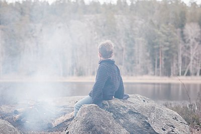 young boy sitting on a rock by a campfire and lake in Sweden - p1166m2179461 by Cavan Images