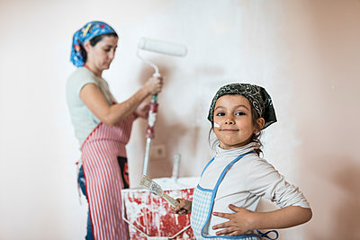 Portrait of little girl painting wall in children's room with her mother - p300m1449605 by Jaen Stock
