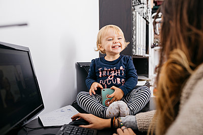 Mother working at home with little daughter sitting on desk - p300m2058909 by Josep Rovirosa