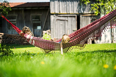 Two children relaxing in hammock in garden of a farm - p300m2081267 von Steve Brookland