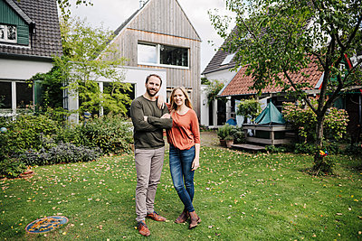 Proud home owners standing in their garden - p300m2166677 by Kniel Synnatzschke