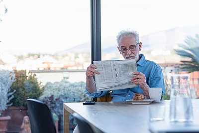 Senior man reading newspaper while sitting by table at home - p300m2265089 by Emma Innocenti