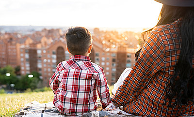 Mother and son looking at view while sitting on hill during sunset - p300m2287736 by Jose Carlos Ichiro