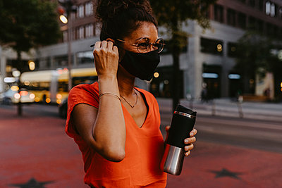 Businesswoman with protective face mask and insulated container in city - p426m2239114 by Maskot