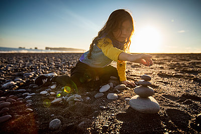 Little girl stacking wish stones, black sand beach, Reynisfjara, Iceland - p429m2145597 by Romona Robbins Photography