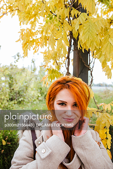 Portrait of smiling young woman with orange dyed hair in autumn - p300m2156440 by DREAMSTOCK1982