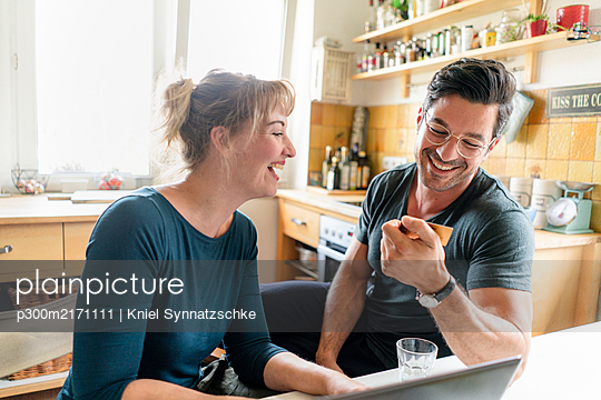 Happy couple shopping online in kitchen at home - p300m2171111 by Kniel Synnatzschke