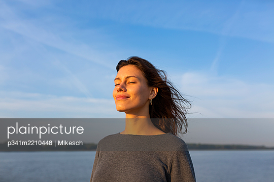 Young woman at the Elbe river, portrait - p341m2210448 by Mikesch