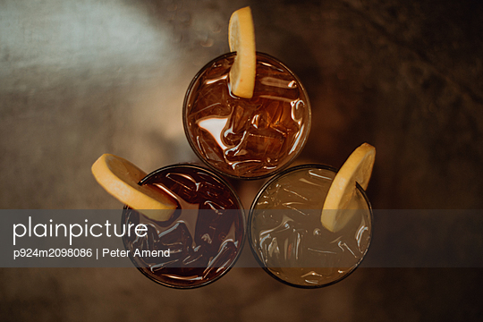 Three glasses of iced fruit drinks on cafe table, overhead view - p924m2098086 by Peter Amend