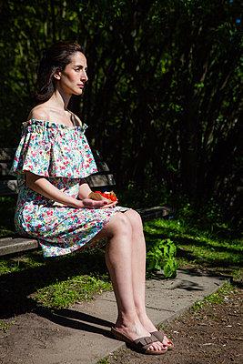 Frau sitzt mit Erdbeeren auf einer Parkbank - p045m2008428 von Jasmin Sander