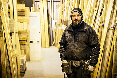 Bearded man wearing beanie and tool belt standing next to a stack of wooden planks in a warehouse, looking at camera. - p1100m1575751 by Mint Images
