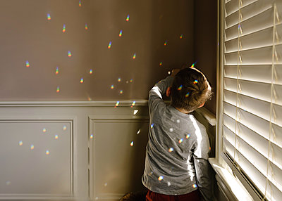 Boy playing with spectrum while standing by window - p1166m1489521 by Cavan Images