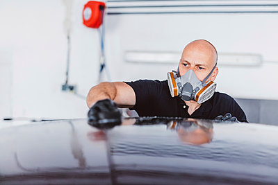 Male worker wearing protective mask while cleaning car roof in workshop - p1166m2060374 by Cavan Images