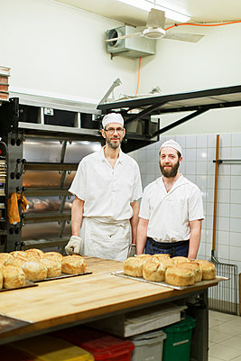 Sweden, Bakers standing next to table with baked bread - p352m1079180f by Christian Ferm