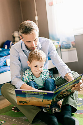 Father reading book to son while sitting on floor at home - p426m1179355 by Kentaroo Tryman