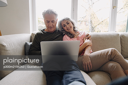 Happy senior couple with laptop relaxing on couch at home - p300m2156263 by Gustafsson